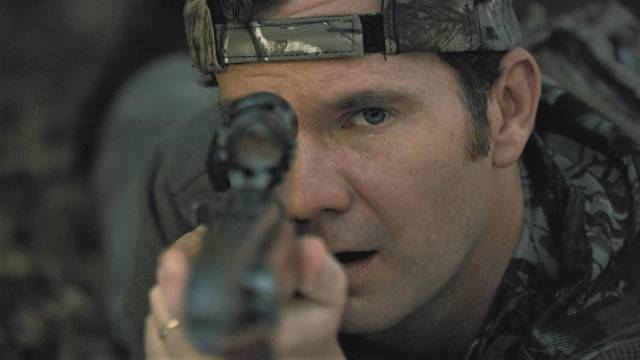 ... and suburban dad Chris Cleek (Sean Bridgers) spots her through his hunting rifle sight in Lucky McKee's The Woman (2011)