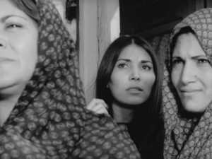 Seamstress Ati (Parvaneh Massoumi) watches the new teacher's arrival in Bahram Beyzaie's Downpour (1972)
