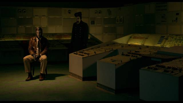 The virus (Ciaron Davies) interrogates Agent Palmer Eldritch (Agastin Mateo) in Miguel Llanso's Jesus Shows You the Way to the Highway (2019)