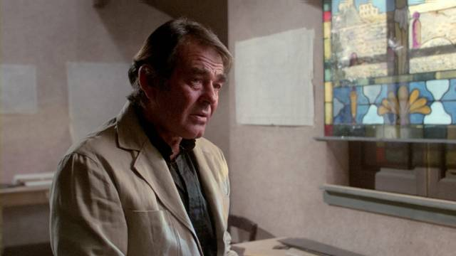 Former rugged leading man Stuart Whitman as Father Cunningham, a weary priest fighting evil in Alfredo Zacarias' Demonoid (1981)