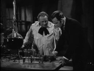 Professor Le Blanc (Wallace Evennett) and Lucien Cortier (John Warwick) watch electricity revive dead tissue in George King's The Face in the Window (1939)