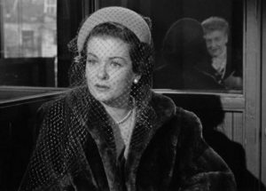 Trying to raise money, Lucia (Joan Bennett) is asked awkward questions at a no-questions-asked loan company in Max Ophuls' The Reckless Moment (1949)