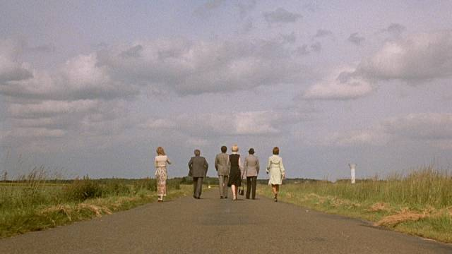 The group of friends wander endlessly in search of a good meal in Luis Bunuel's The Discreet Charm of the Bourgeoisie (1972)