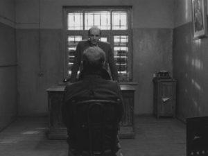 Portnov (Anatoliy Solonitsyn) interrogates Sotnikov (Boris Plotnikov) with implacable cruelty in Larisa Shepitko's The Ascent (1977)
