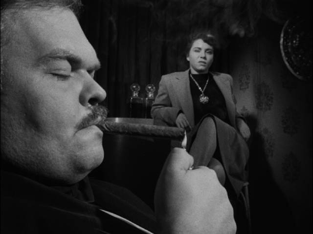 The Fat Man (Bruno Ve Sota) is completely disinterested in the Gamin (Adrienne Barrett) in John Parker's Dementia (1953)