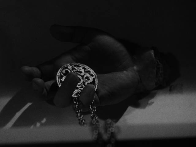 The Gamin (Adrienne Barrett)'s medallion gripped in the Fat Man (Bruno Ve Sota)'s severed hand in John Parker's Dementia (1953)