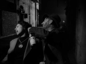 The Gamin (Adrienne Barrett) is assaulted in a back alley in John Parker's Dementia (1953)