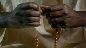 Ibrahim (Makhouredia Gueye) gets comfort from the formal trappings of religion in Ousmane Sembene's Mandabi (1968)