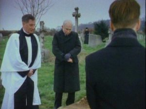 At Mrs. Drablow's funeral, Arthur Kidd (Adrian Rawlins) sees a silent figure watching in Herbert Wise's The Woman in Black (1989)