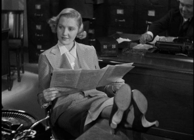Wilhelmina Clark (Jean Arthur) is amused by Arthur (Edward G. Robinson)'s predicament in John Ford's The Whole Town's Talking (1935)