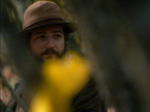 Cookie (John Magaro) counters the harshness of the frontier by baking in Kelly Reichardt's First Cow (2020)