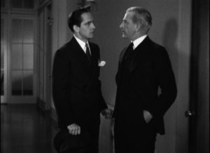 Joan's father (George Irving) tries to turn Jerry (Frederic March) away from her hospital room in Dorothy Arzner's Merrily We Go to Hell (1932)