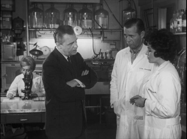 A government agent seeks answers from baffled scientists in Bill Rebane and Herschell Gordon Lewis's Monster a Go-Go (1965)