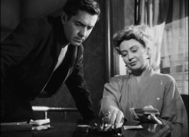 Zeena (Joan Blondell) reads the Tarot and sees something dark ahead for Stan (Tyrone Power) in Edmund Goulding's Nightmare Alley (1947)