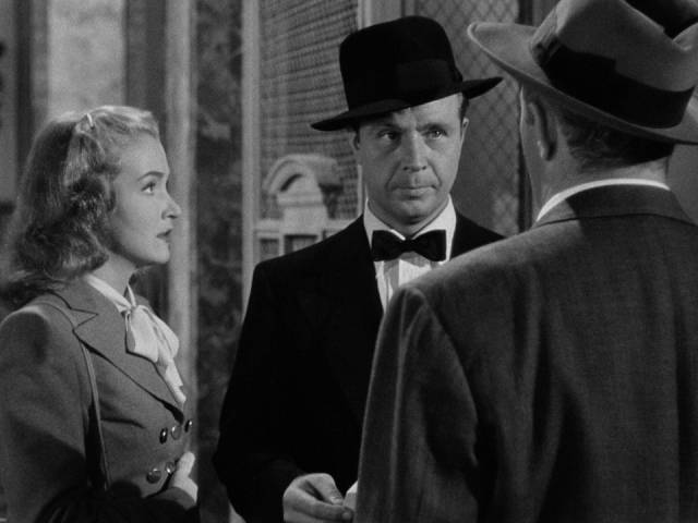 Johnny O'Clock (Dick Powell) is irritated when Inspector Koch (Lee J. Cobb) confronts him in Robert Rossen's Johnny O'Clock (1947)