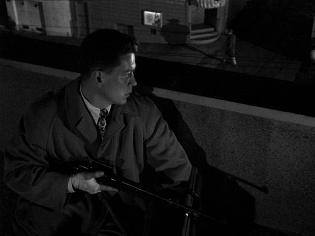 Edward Miller (Arthur Franz) waits for Jean Darr (Marie Windsor) on a rooftop with his rifle in Edward Dmytryk's The Sniper (1952)