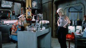 Evil nerd Menlo Schwartzer (Eddie Deezen) explains his plans to sidekick Sparkle (Linda Kerridge) in Randall Badat's Surf II (1983)