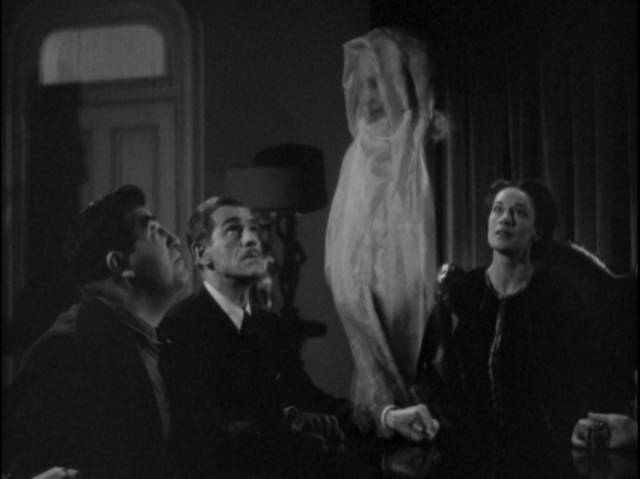 Dr. Blair (Boris Karloff) attends a phony seance conducted by medium Mrs. Walters (Anne Revere) in Edward Dmytryk's The Devil Commands (1941)