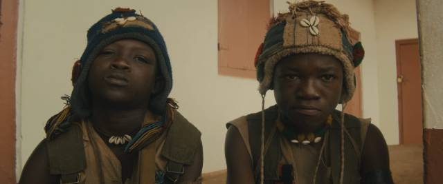 Strika (Emmanuel Nii Adom Quaye) becomes the closest thing to a friend Agu (Abraham Attah) finds in his new life in Cary Joji Fukunaga's Beasts of No Nation (2015)