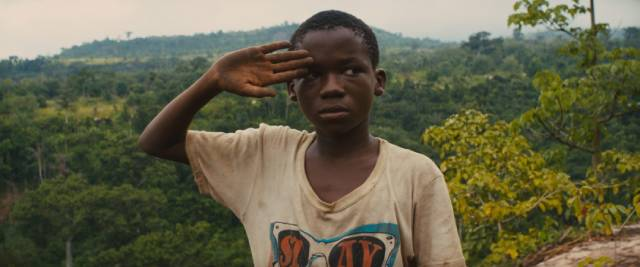 Agu (Abraham Attah) is drafted into the Commandant (Idris Elba)'s battalion in Cary Joji Fukunaga's Beasts of No Nation (2015)