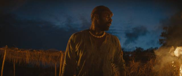 Hints of an apocalyptic future as the Commandant (Idris Elba) orders the destruction of his battalion's camp in Cary Joji Fukunaga's Beasts of No Nation (2015)