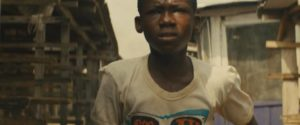 Agu (Abraham Attah) runs for his life after his family is murdered in Cary Joji Fukunaga's Beasts of No Nation (2015)