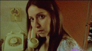 Altair (Diana Bovio) answers a vaguely menacing phone call in Victor Dryere's 1974: La posesión de Altair (2016)