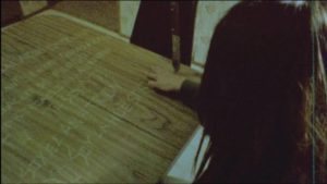 In a trance, Altair (Diana Bovio) carves words into the kitchen table in Victor Dryere's 1974: La posesión de Altair (2016)