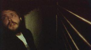 Friend Callahan (Guillermo Callahan) tries to hide from intruders in Victor Dryere's 1974: La posesión de Altair (2016)