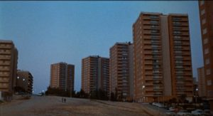 Modern housing overlooks the wasteland where Marcos (Vicente Parra) lives in Eloy de la Iglesia's The Cannibal Man (1982)